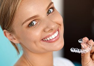 Smiling woman holding Invisalign tray