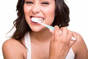 young attractive woman smiling brushing teeth