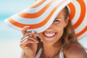 Smiling woman in sun hat with porcelain veneers near Palmer
